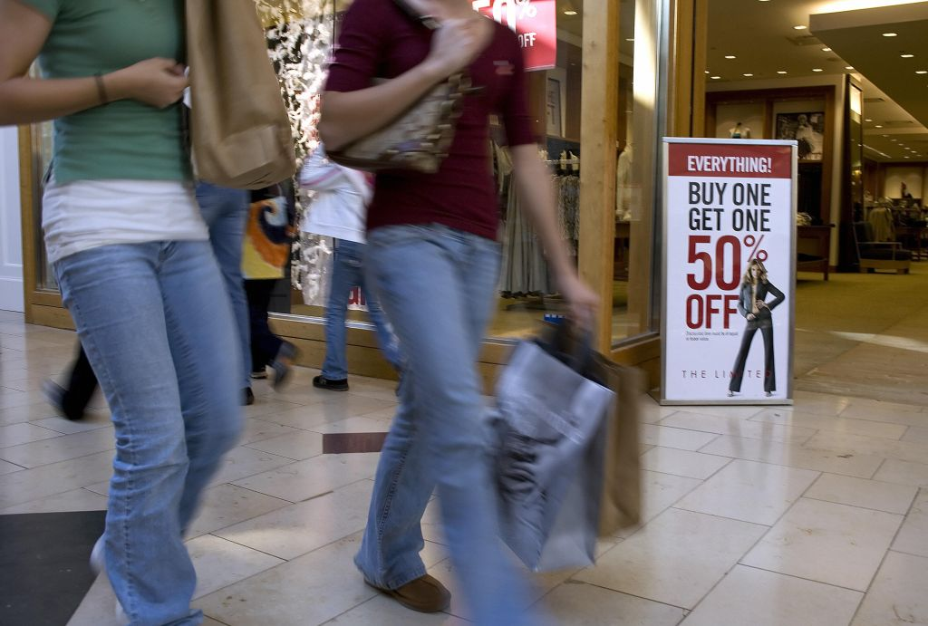 Shoppers walk past a sale sign in front