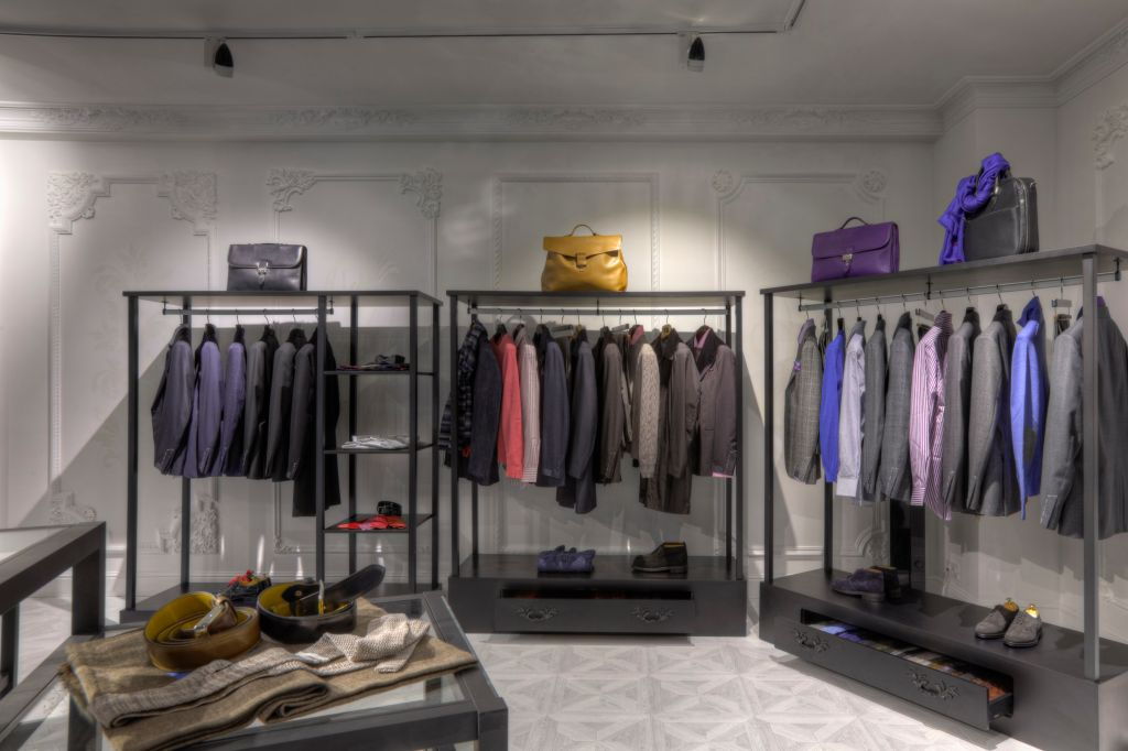 Suits and shoes on racks in clothing store for men