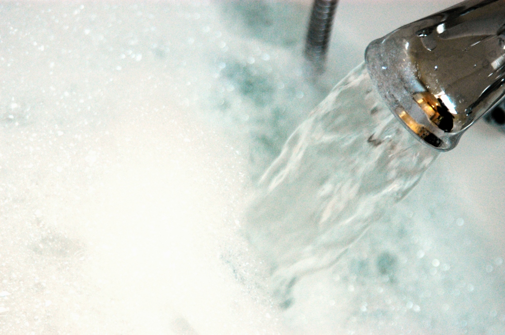 Water gushing from tap into bath containing bubble bath