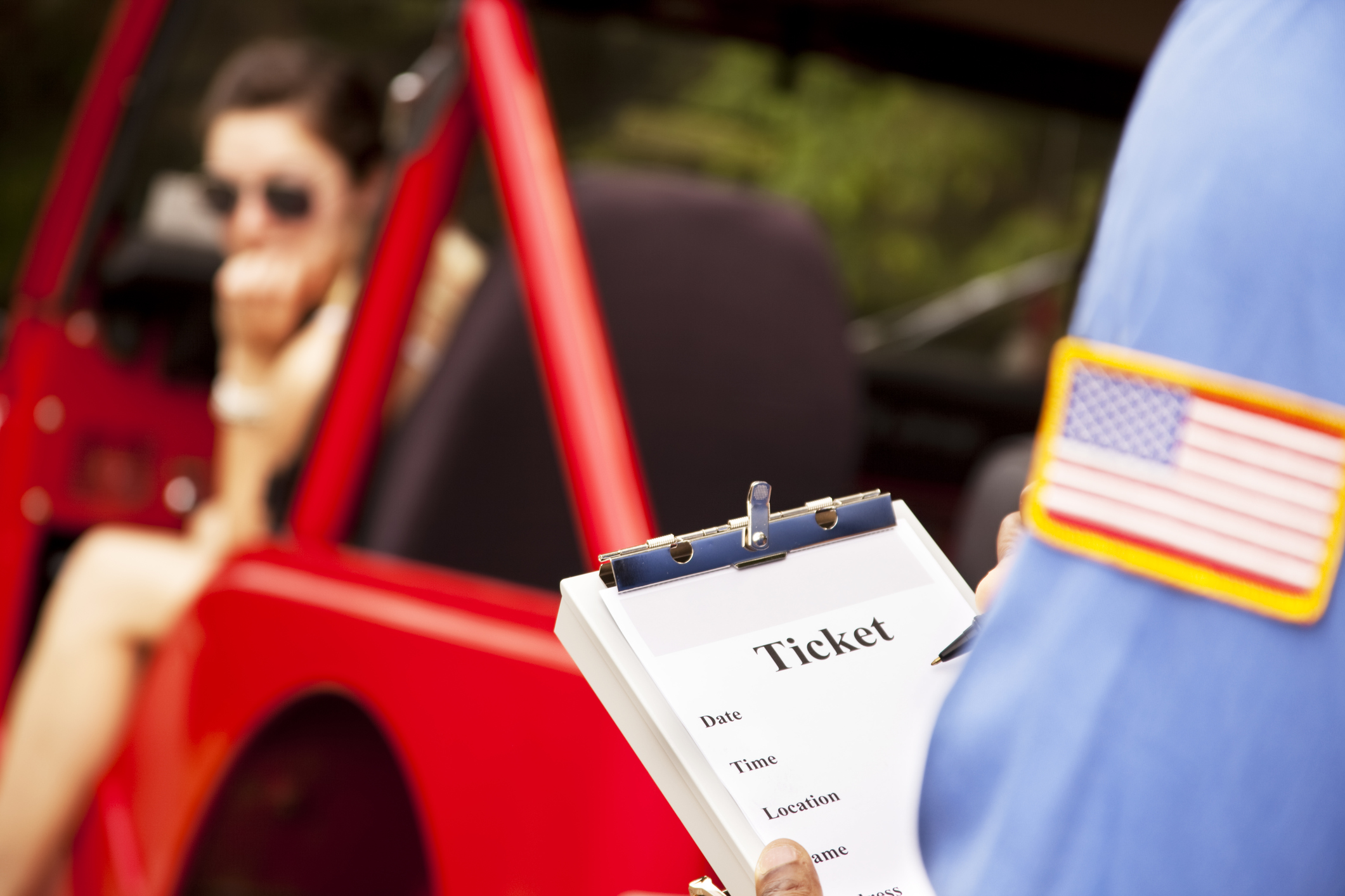 Caucasian female in red vehicle getting a ticket from policeman