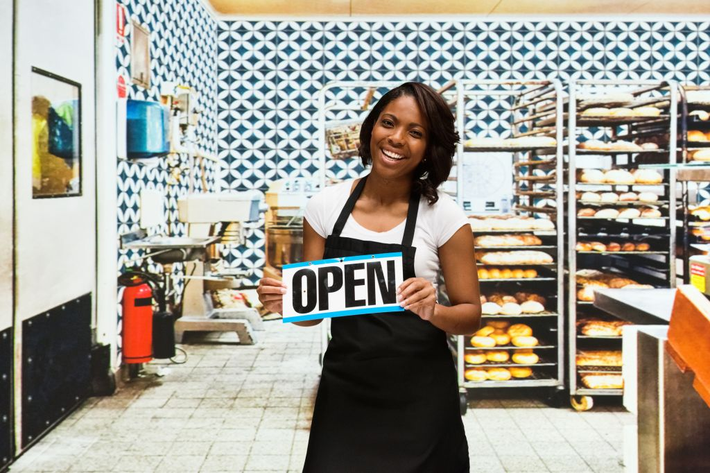 Smiling baker holding open sign in bakery
