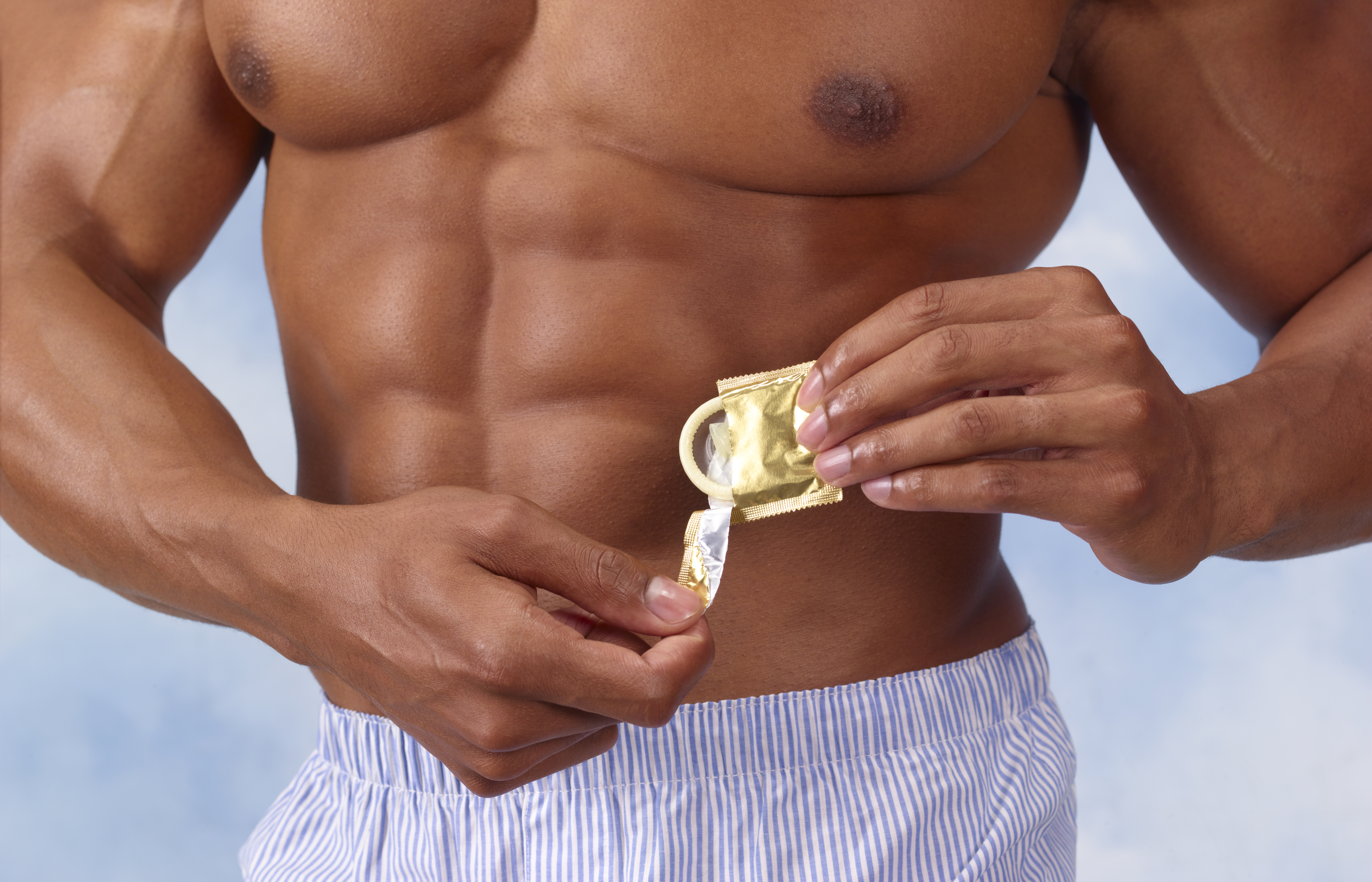 muscular man opening condom packet