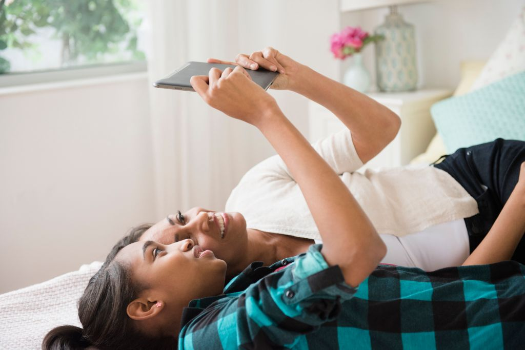 Mother and daughter laying on bed using digital tablet