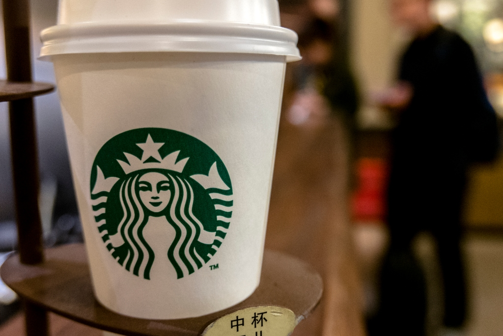 A Starbucks coffee cup on table. Starbucks is growing fast...