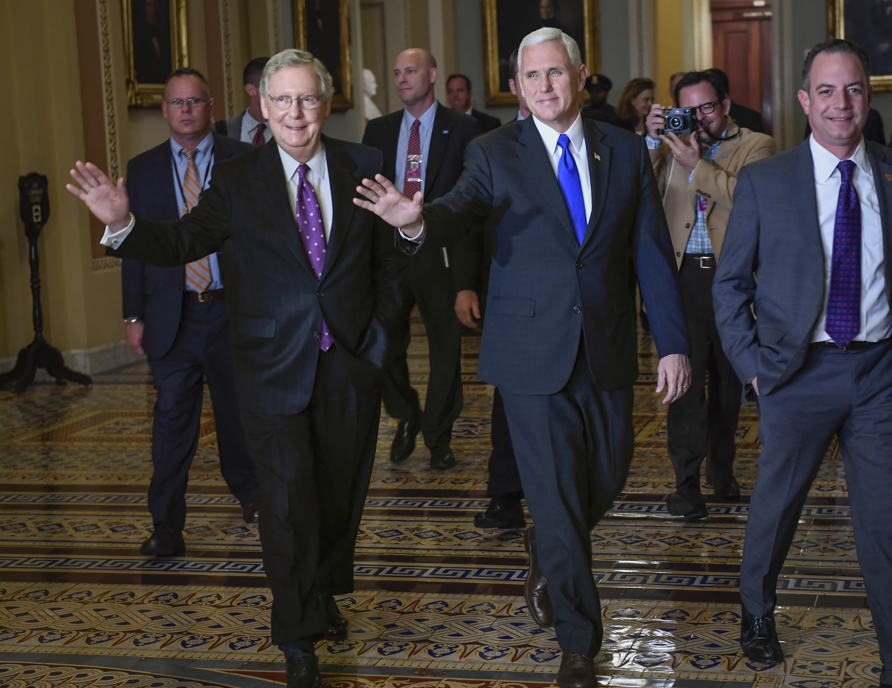 Senate Majority Leader Mitch McConnell walks through the Capitol with Vice-President elect Mike Pence, in Washington, DC.