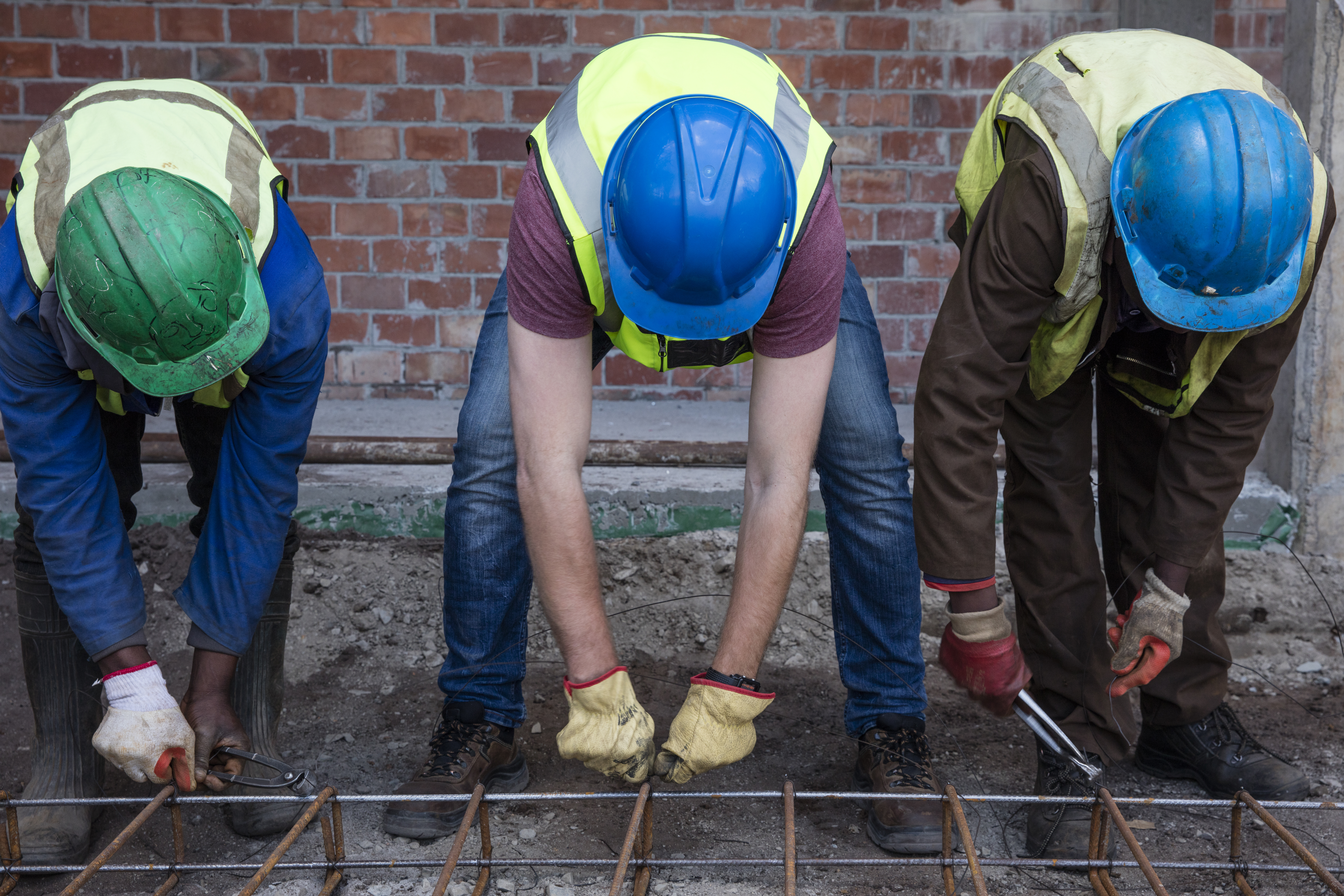 Construction workers on a construction site assembling reinforcing steel
