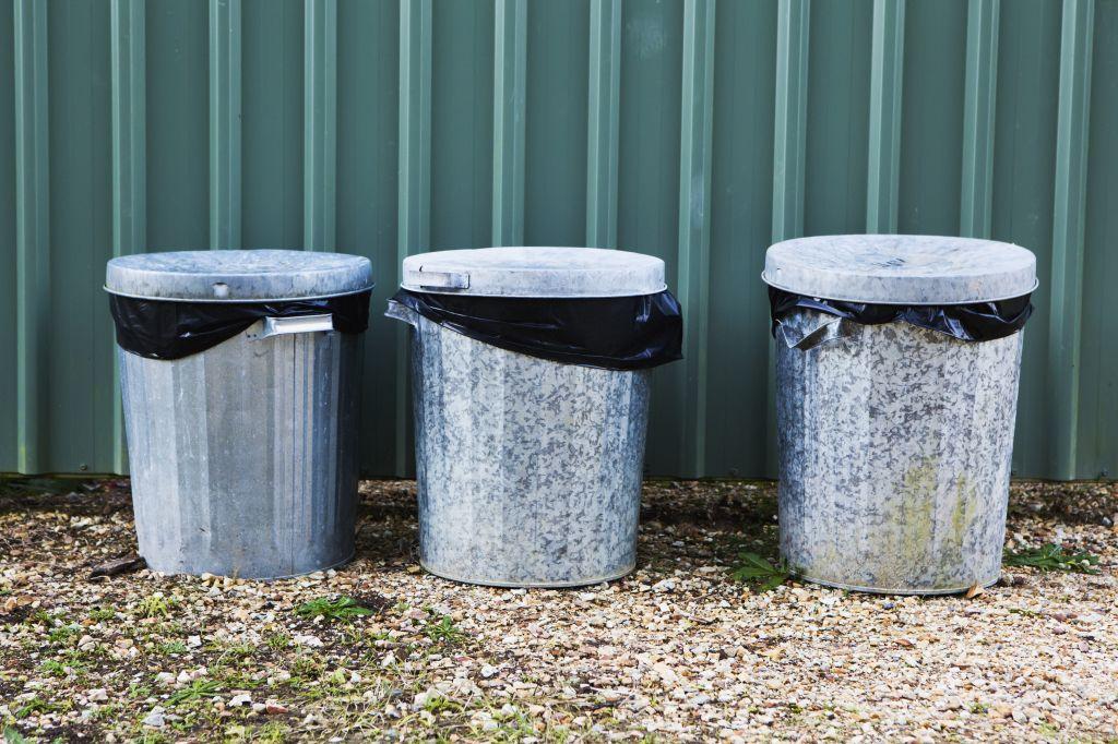 Metal Garbage Bins In A Row Against A Metal Wall