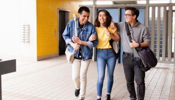 Three highschool friends walking to class.