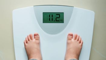 Low Section Of Child Standing On Weight Scale