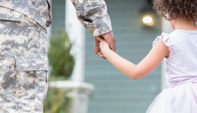 Army dad holds hands with young daughter