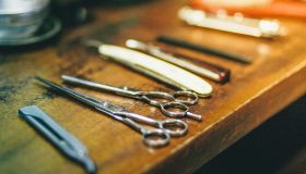 Barbers scissors and razors on wooden surface, close-up