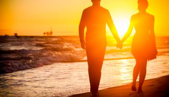 Diverse couple walking on beach at sunset