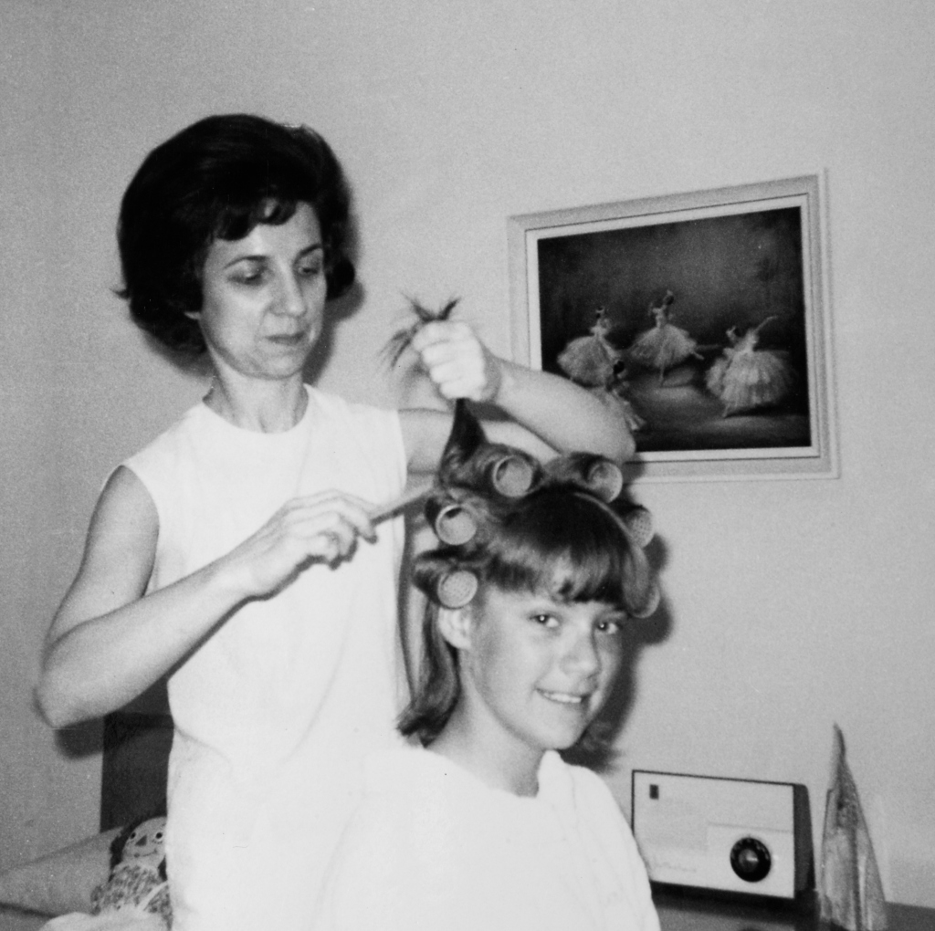 Mother helps 16 year old daughter get ready for date, ca. 1970