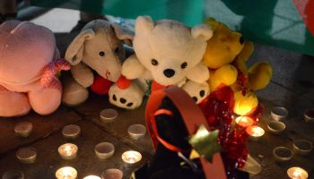 People leave assorted toys and candles in the memory of the...
