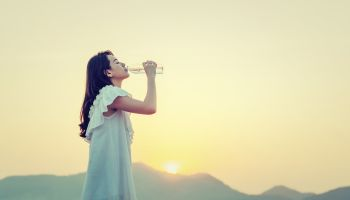 Side View Of Young Woman Drinking Water While Standing Against Sky During Sunset