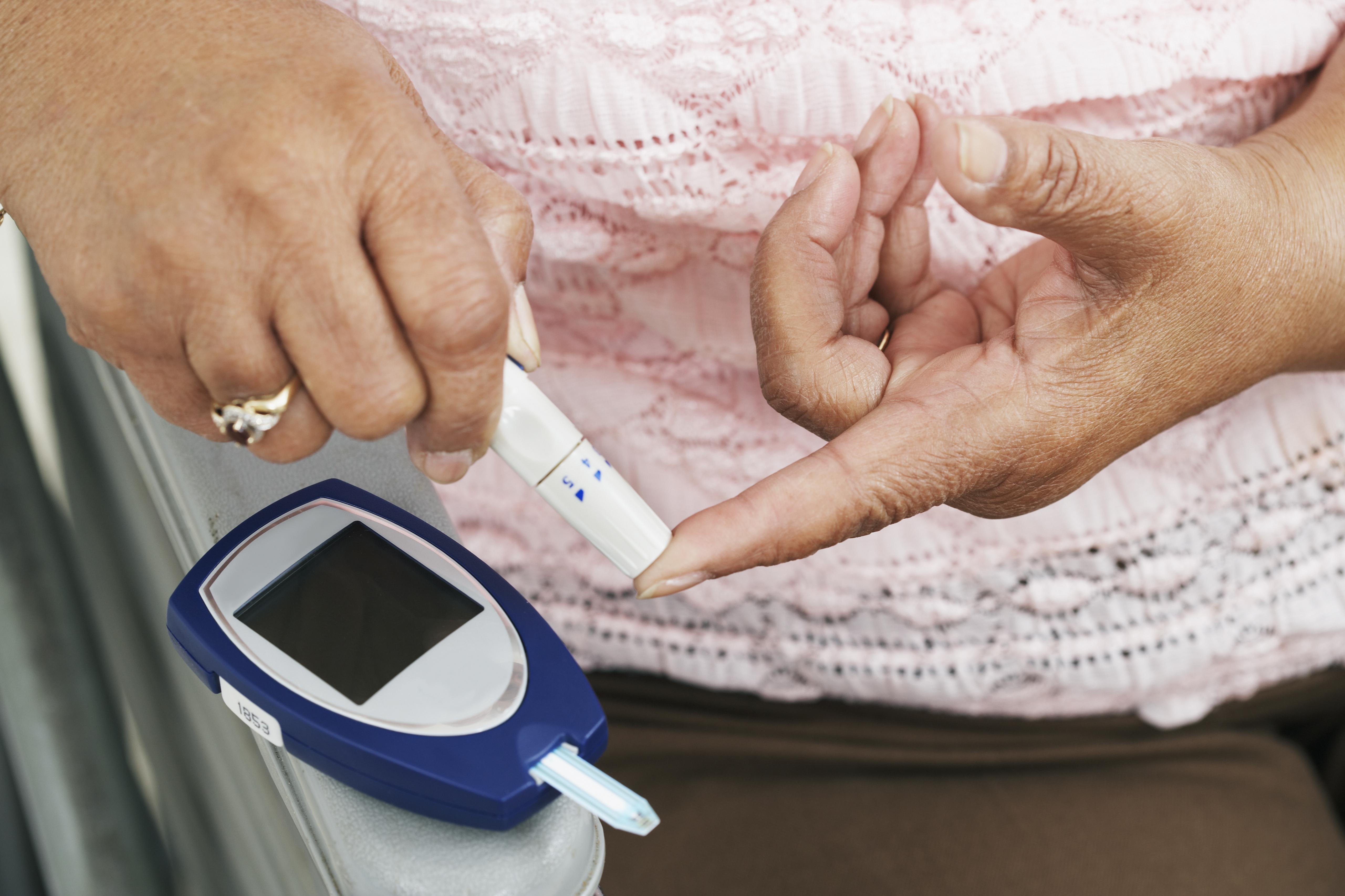 Senior African American woman testing blood sugar