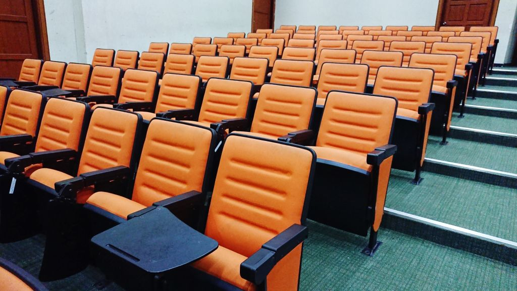 Empty Orange Chairs In Auditorium