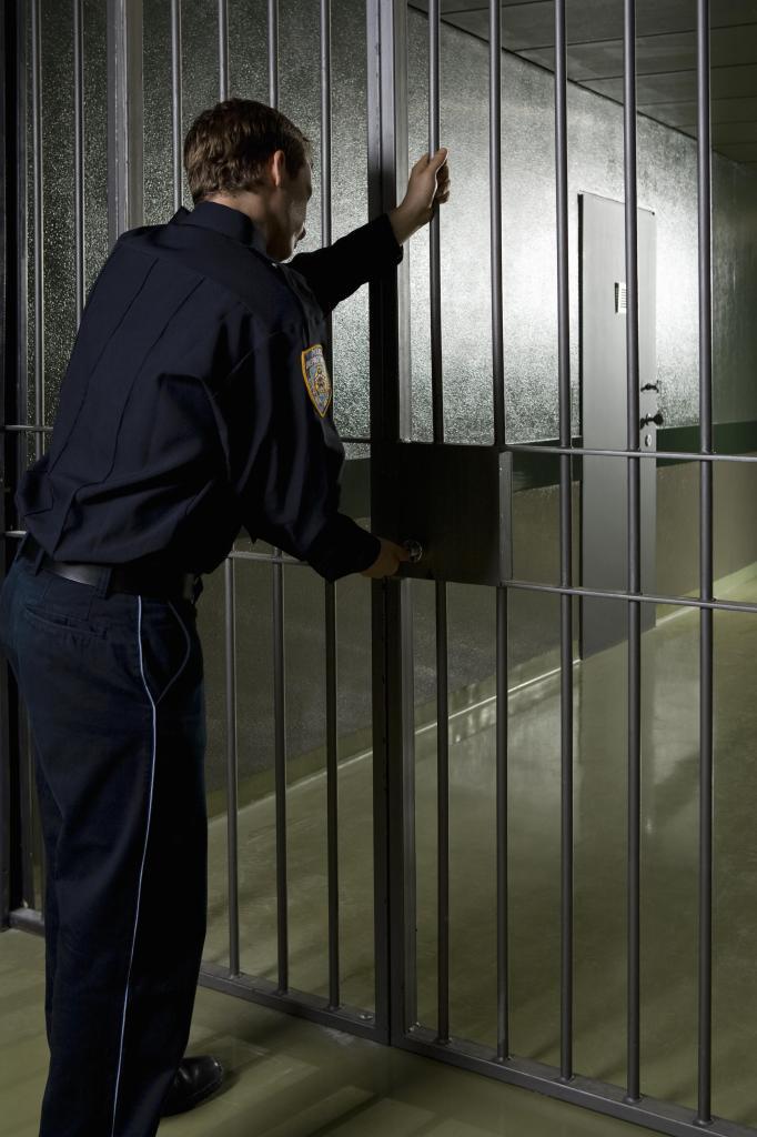 A prison guard locking a prison door