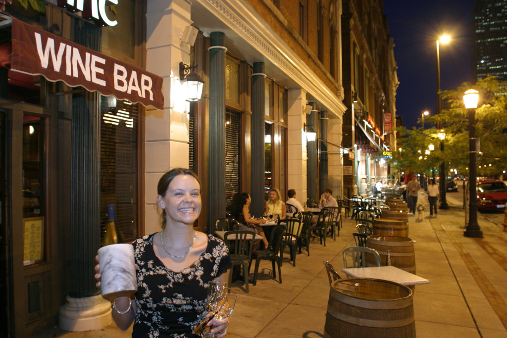 A woman holding a bottle of wine outside a wine bar in the Warehouse District.