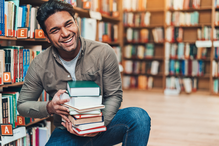 Happy young man with a pile of books in a bookstore