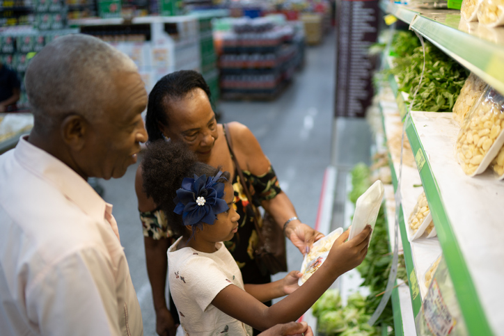 Family choosing vegetables at grocery store