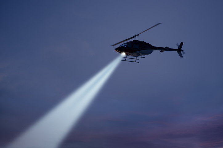 Police helicopter shining a light beam in the dark sky