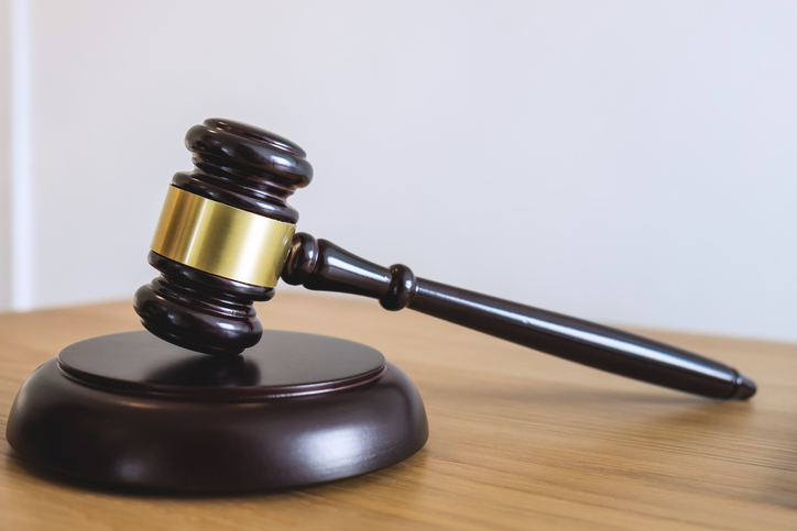 Close-Up Of Gavel On Table Against White Background