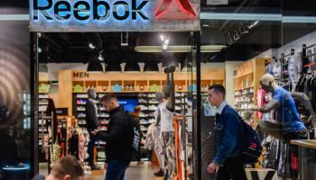 People are seen next to the Reebok shop...