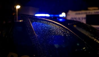 Spain, Madrid, rain falling on the window of police car at night