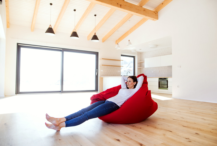 Young woman sitting on a bean bag in living room in a new home, resting.