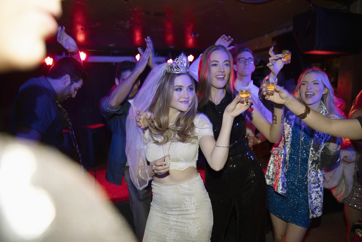 Bachelorette and friends dancing and drinking in nightclub