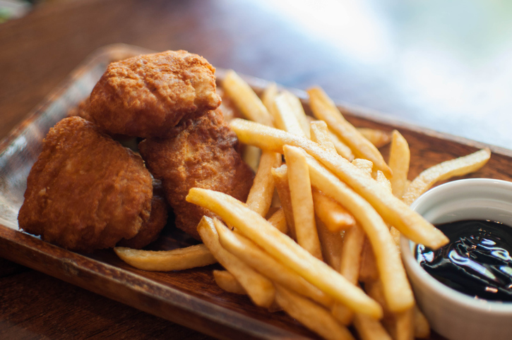 Chicken nuggets and fries on a wooden table