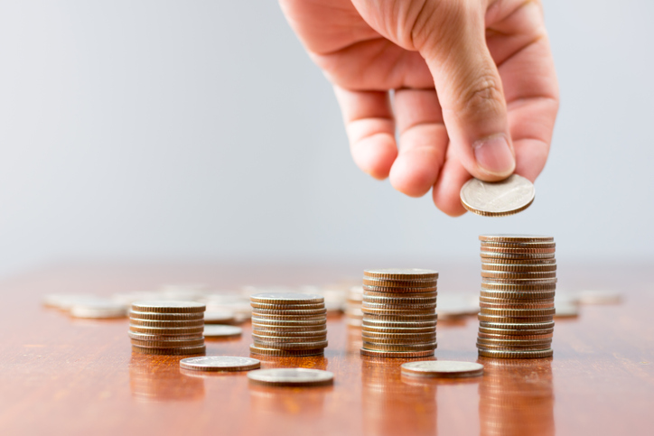 Close-Up Of Hand Stacking Coins On Table Against Wall