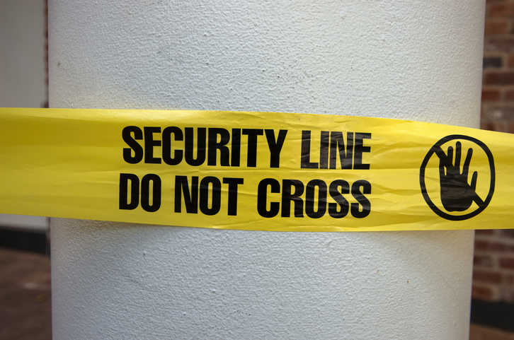'Security line - do not cross' plastic cordon tape around a pillar
