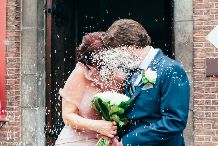 Petals Falling On Groom And Bride With Bouquet Standing Outside Building