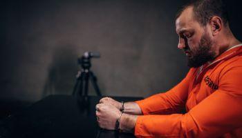 Prisoner sitting in interrogation room alone