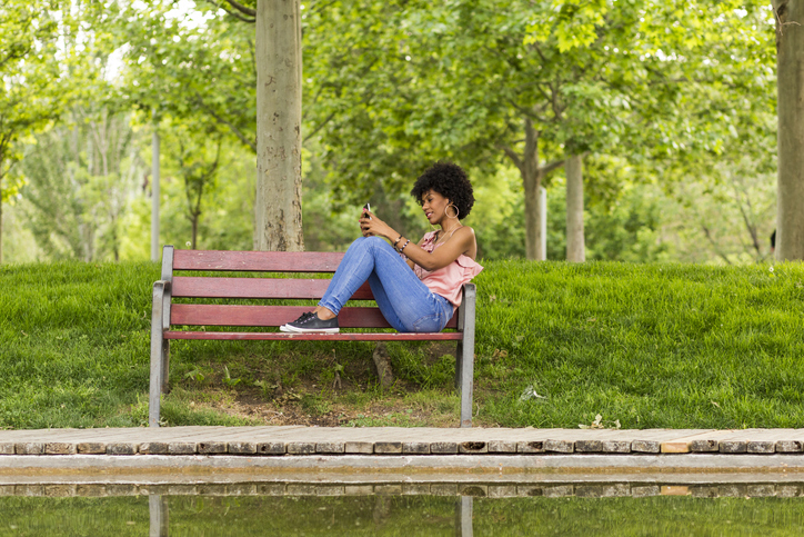 Smiling Woman Using Mobile Phone While Sitting On Wooden Bench At Park