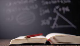 pen on open book in classroom
