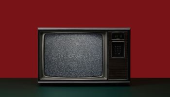 Vintage Analog Television Set with Static on the Screen on Green Surface on Red Background
