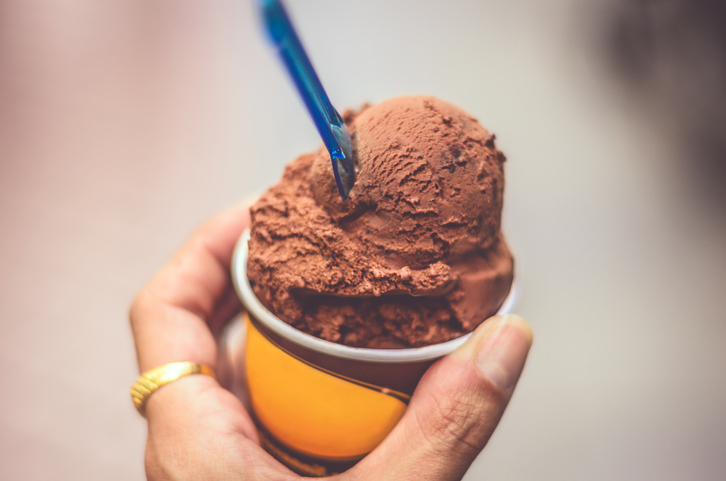 Close-Up Of Hand And Chocolate Ice Cream
