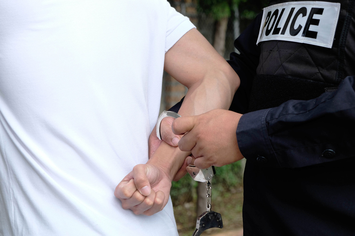 Midsection Of Policeman Wearing Handcuffs To Criminal
