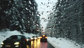 Cars On Road Amidst Trees Seen Through Wet Windshield During Winter