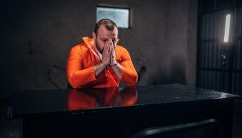 Prisoner in orange jumpsuit sitting alone in interrogation room