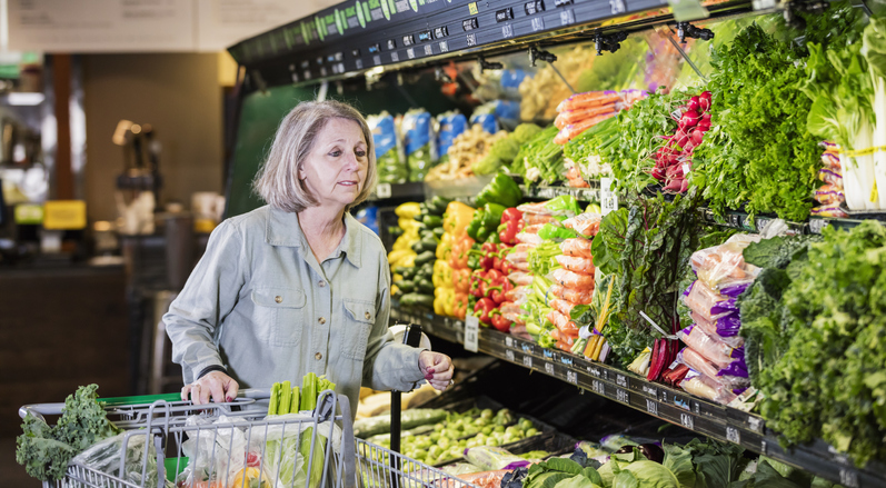 Senior woman shopping in produce aisle of grocery store