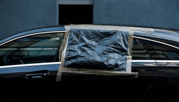 Broken car window fixed with plastic foil and tape