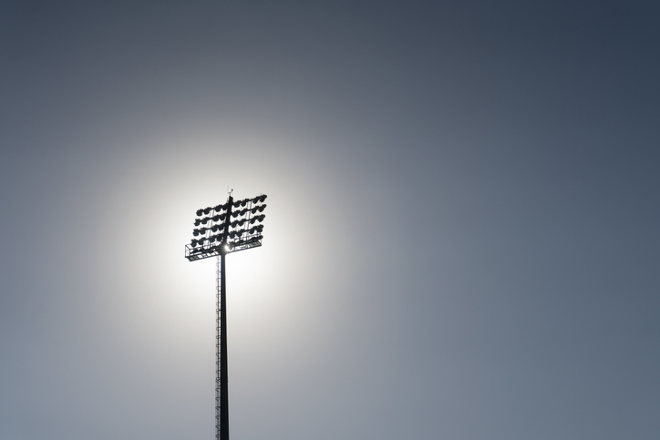 Afternoon sun shines behind stadium lights