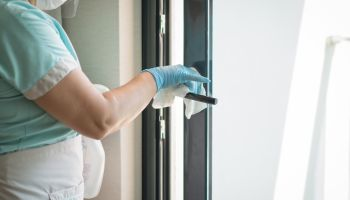 Maid cleaning doorknob and wearing a face mask