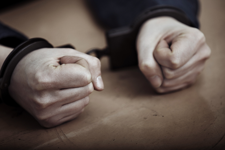 Hands of arrested man in handcuffs