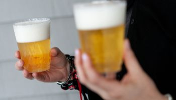 Woman holding two frothy cups of beer