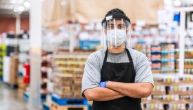 Food warehouse employee wearing a protective face mask and a face shield